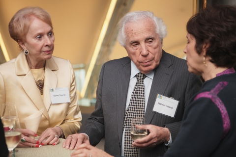 Seymour Topping and his wife, Audrey, speak with ICFJ President Joyce Barnathan at an ICFJ event.